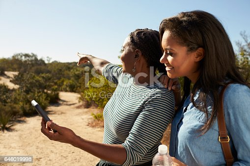 904170246 istock photo Mother And Adult Daughter Navigate With Mobile Phone On Walk 646019998