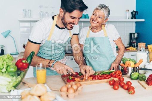 istock Mother and adult son making salad together 1070848162
