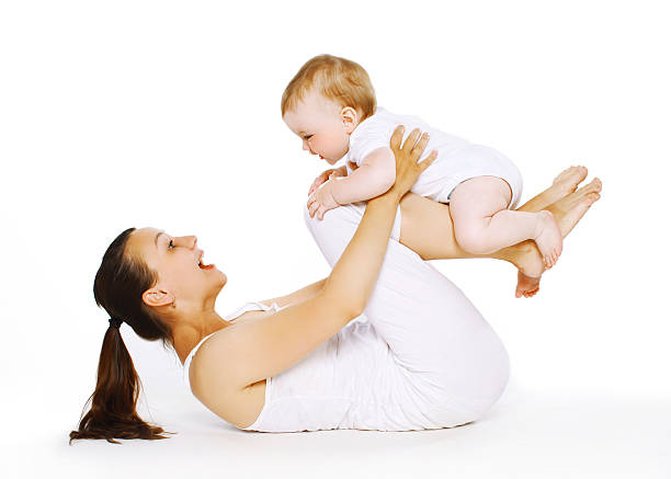 Mother and baby are doing exercise, gymnastics, fitness stock photo