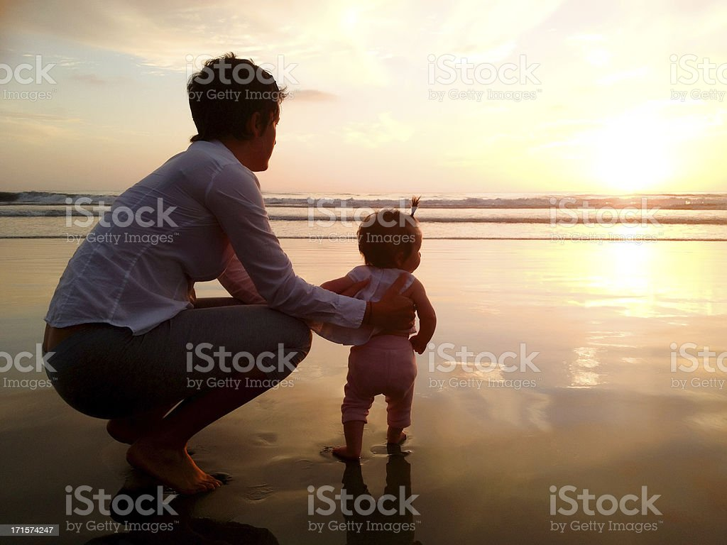 Mother and baby at beach stock photo