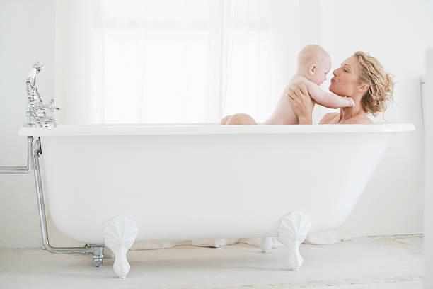 mother and baby bathing - baby bathtub bildbanksfoton och bilder