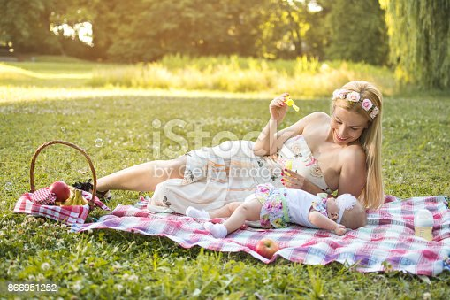 507271044istockphoto Mother and baby blowing bubbles in the park. 866951252