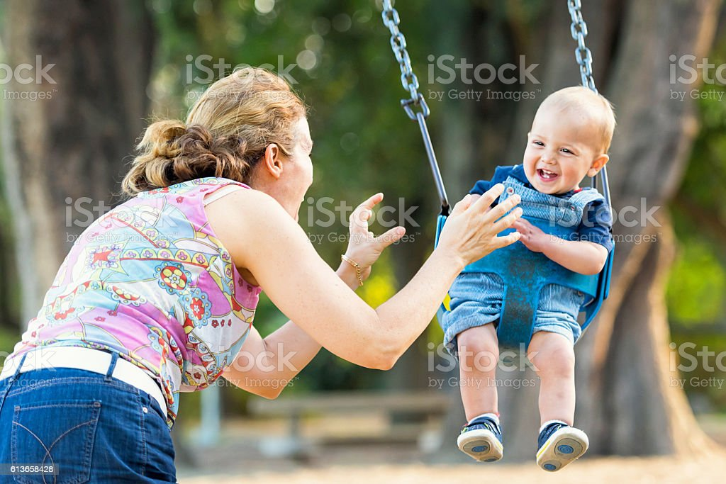 Mother and baby boy having fun in a park stock photo