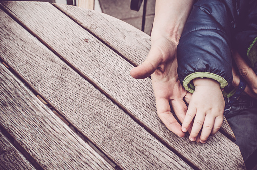 istock Mother and baby child holding hands on wooden table background 517848078
