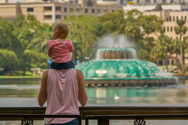 Mother and Baby Daughter at Lake Eola Park and the Orlando Skyline in Downtown Orlando Florida USA stock photo