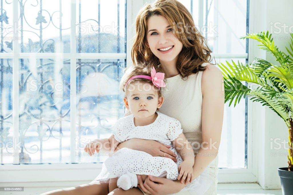Hija de madre y bebé feliz y hermosa Inicio juntos jugando en el piso en el fondo de la ventana - foto de stock