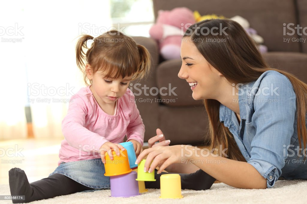 Mother and baby daughter playing at home stock photo