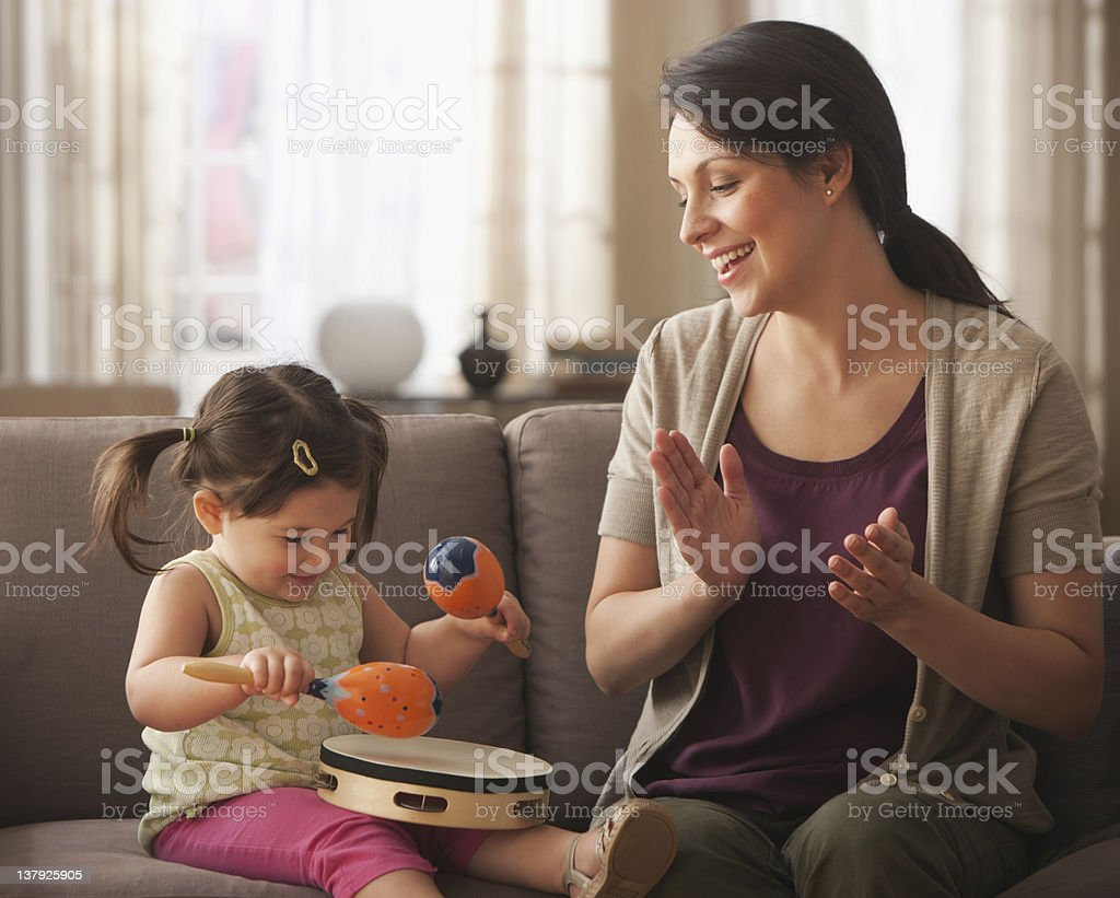 Mother and baby daughter playing with instruments stock photo