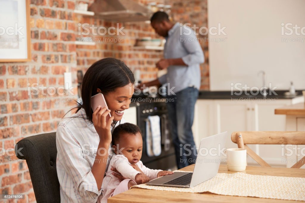 Mother And Baby Daughter Use Laptop As Father Prepares Meal stock photo