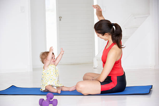 Mother and baby doing yoga stock photo