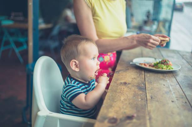 mutter und baby essen in ein café mit fenster - kinderstuhl und tisch stock-fotos und bilder