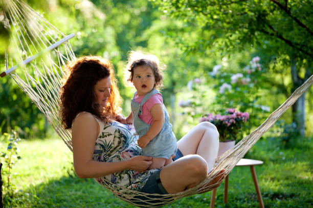 mother and baby girl in hammock enjoying beautiful sunny day - tamara dragovic stock photos and pictures