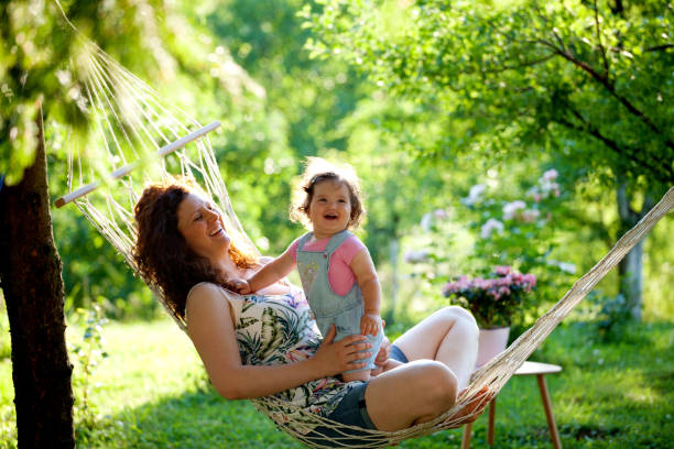 mother and baby girl in hammock laughing - tamara dragovic stock photos and pictures
