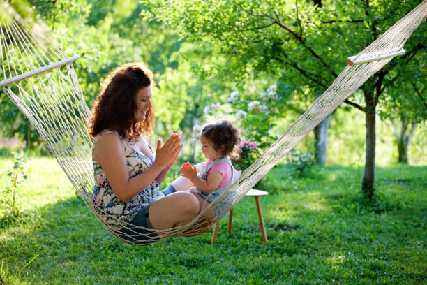 mother and baby girl in hammock playing - tamara dragovic stock photos and pictures