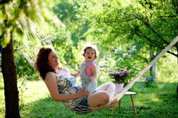 mother and baby girl in hammock smiling - tamara dragovic stock photos and pictures