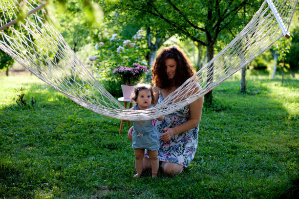 mother and baby girl in the garden enjoying beautiful sunny day - tamara dragovic stock photos and pictures