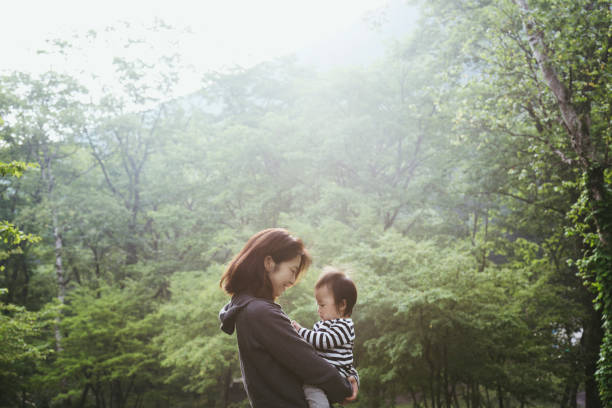 Mother and baby girl relaxed in forest stock photo