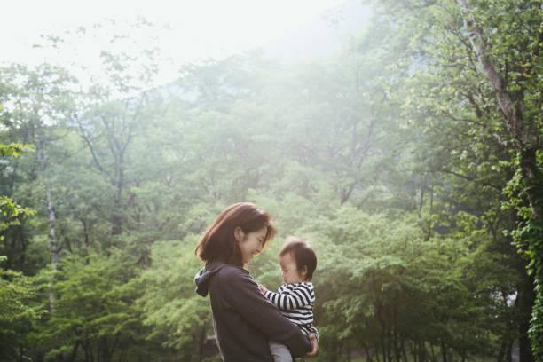 Mãe e filho relaxado em uma floresta - foto de acervo