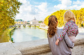 Happy mother and baby girl sightseeing on bridge ponte umberto I with view on basilica di san pietro. rear view