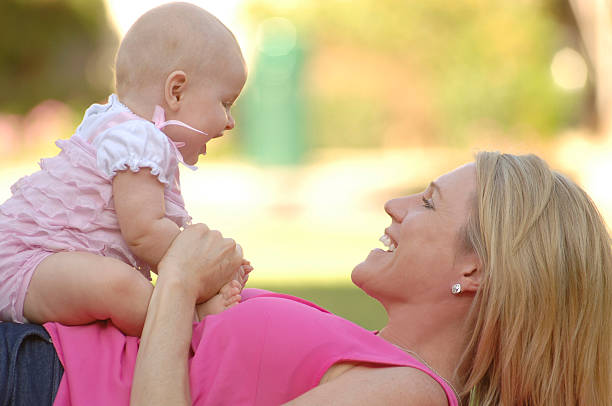 Mother and Baby Girl Smiling at Eachother stock photo