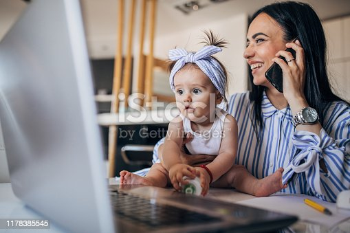 Mother and baby girl working on laptop and using phone. Working mother concept