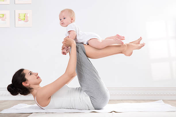 mother and baby gymnastics stock photo