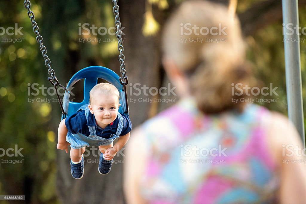 Mother and baby having fun in a park stock photo