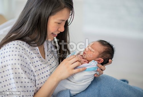 A mother and newborn baby boy are indoors in a hospital room. The mother is laying in bed and smiling down at her baby in her arms. The baby is sleeping.