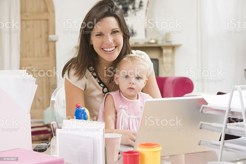 Mother and baby in home office with laptop stock photo