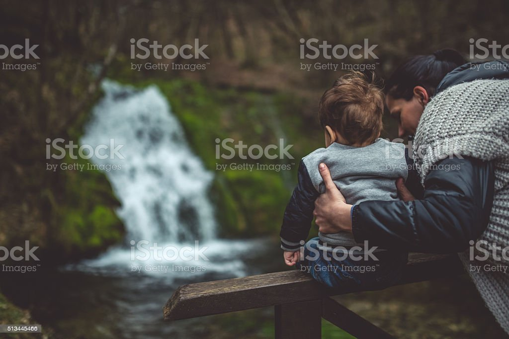 Mother and baby in nature by watefall stock photo