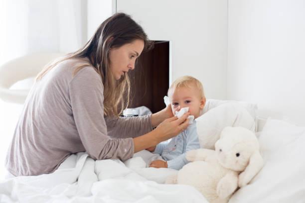 Madre y bebé en pijamas, temprano en la mañana, mamá cuidando a su niño enfermo niño - foto de stock
