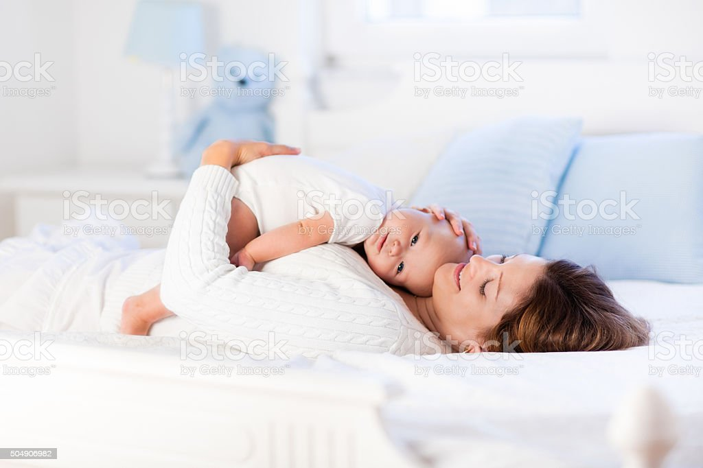 Mother and baby on a white bed stock photo