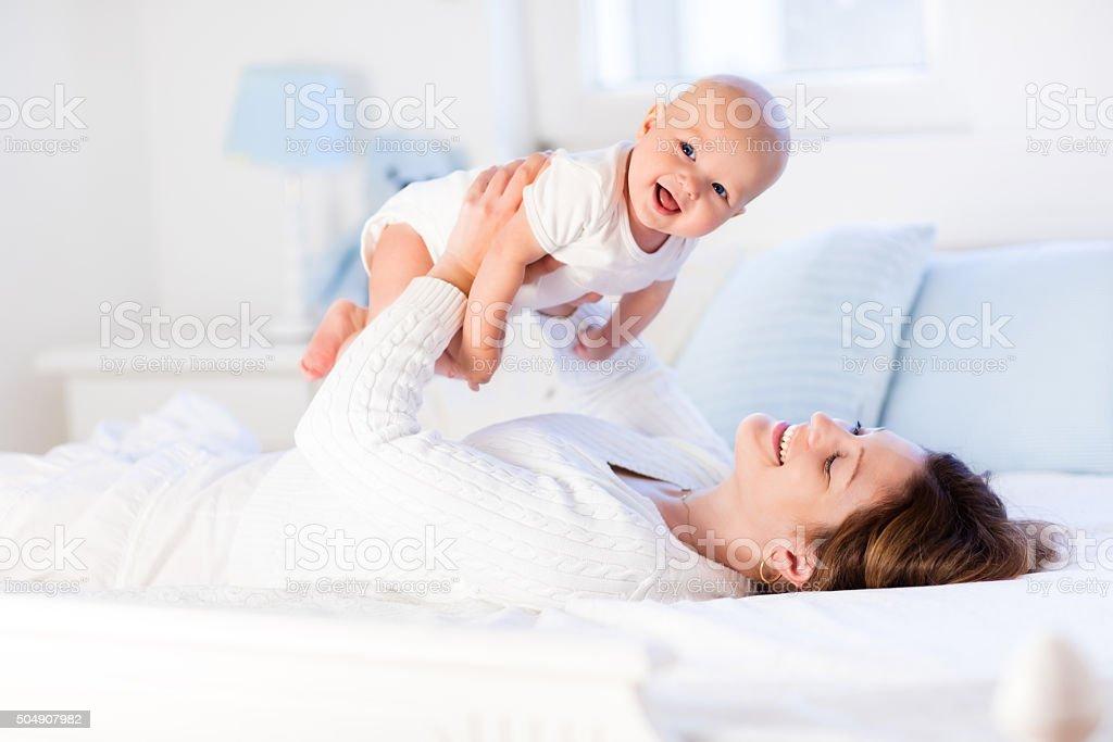 Mutter und baby auf einem weißen Bett – Foto