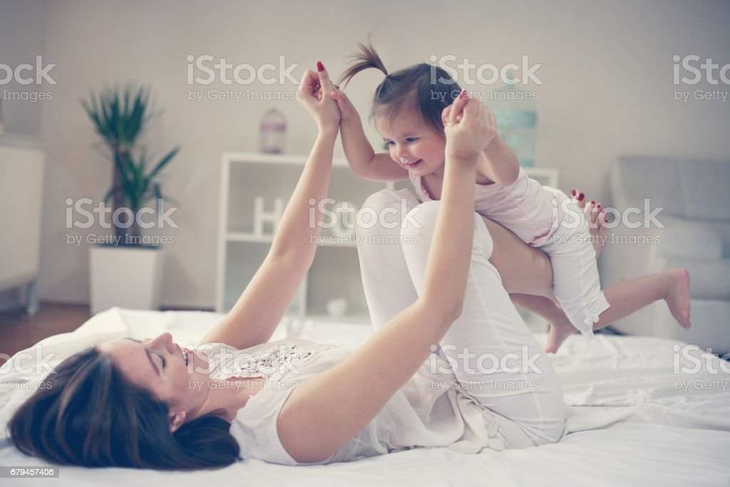 Mother and baby playing in the bed. royalty-free stock photo