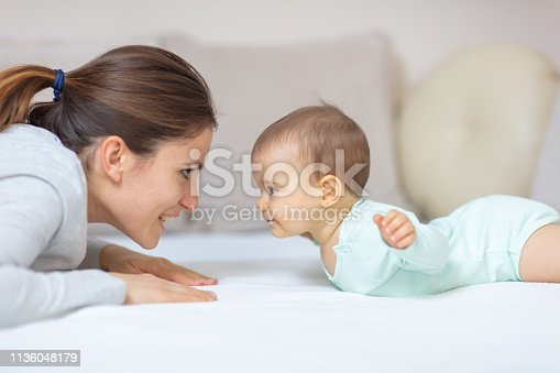 Mother and 7 months old baby doing exercises on the bed and learning to crawl