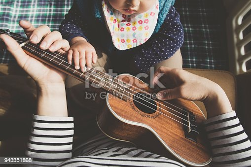 869795984 istock photo Mother and baby playing ukulele at home 943351868