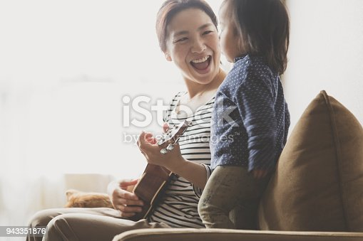istock Mother and baby playing ukulele at home 943351876