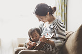 Asian mother and daughter playing ukulele on the sofa.