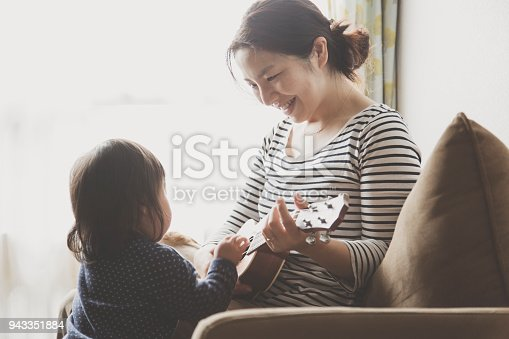 istock Mother and baby playing ukulele at home 943351884
