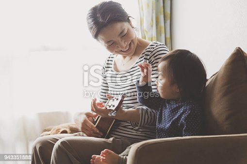 istock Mother and baby playing ukulele at home 943351888