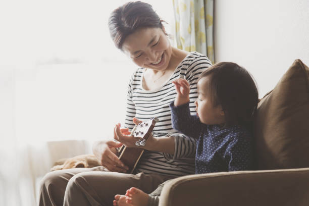 母子家庭でウクレレを演奏 - シンプルな暮らし ストックフォトと画像