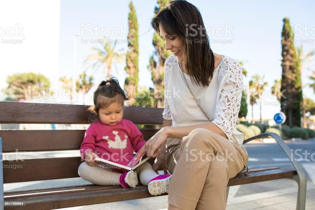Mother and baby reading a book outdoors. royalty-free stock photo