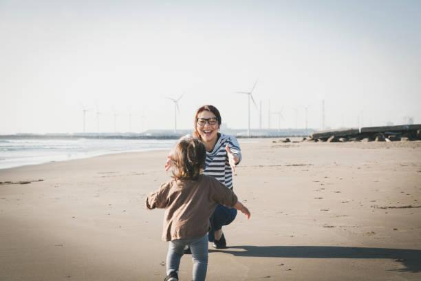 Mãe e bebê relaxados na praia perto de parque eólico - foto de acervo