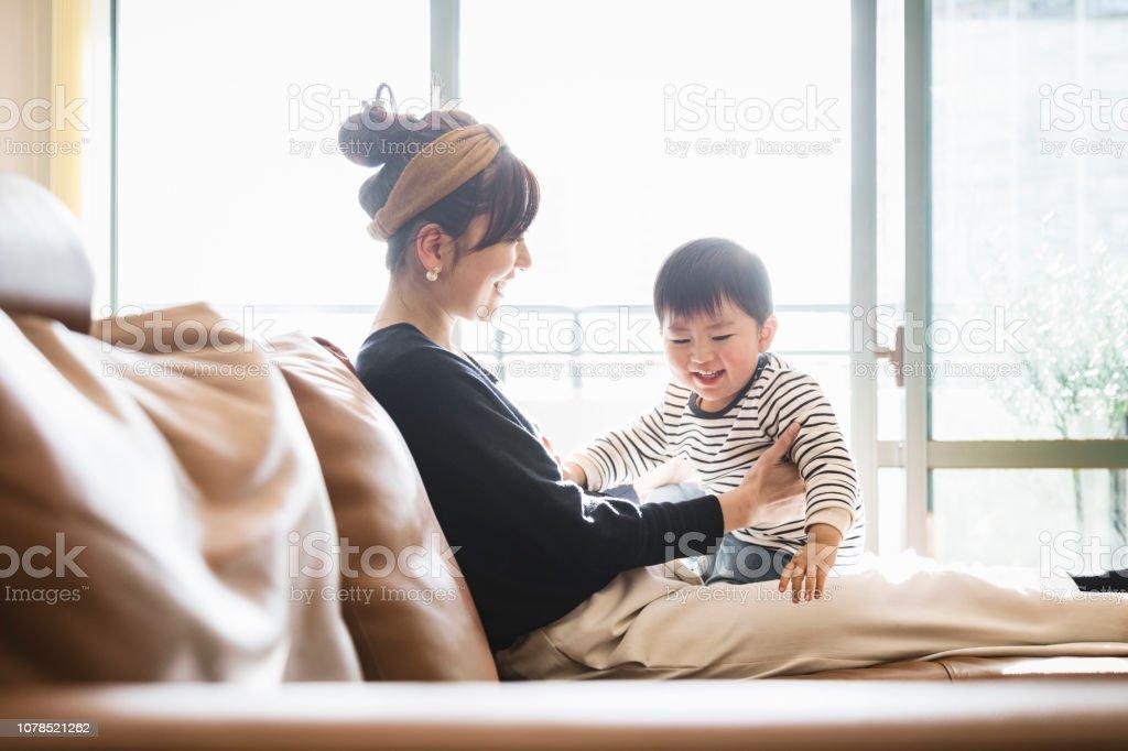 母親と赤ちゃんがソファでリラックス - 2人のロイヤリティフリーストックフォト
