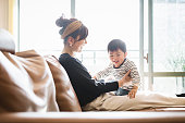 Asian mother and baby communicating in the living room.