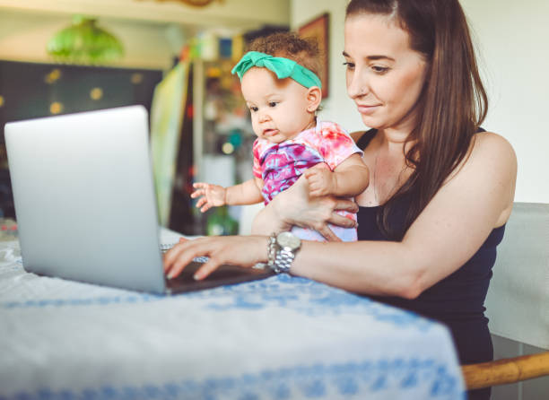 Mother and baby sit in front of a laptop at home, working, video chat or telemedicine stock photo