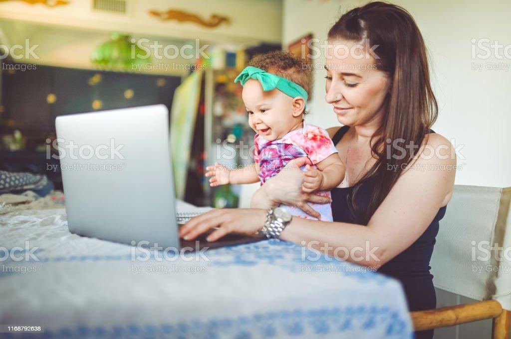 La mère et le bébé s'asseyent devant un ordinateur portatif à la maison, travaillant, chat vidéo ou télémédecine - Photo de 6-11 mois libre de droits