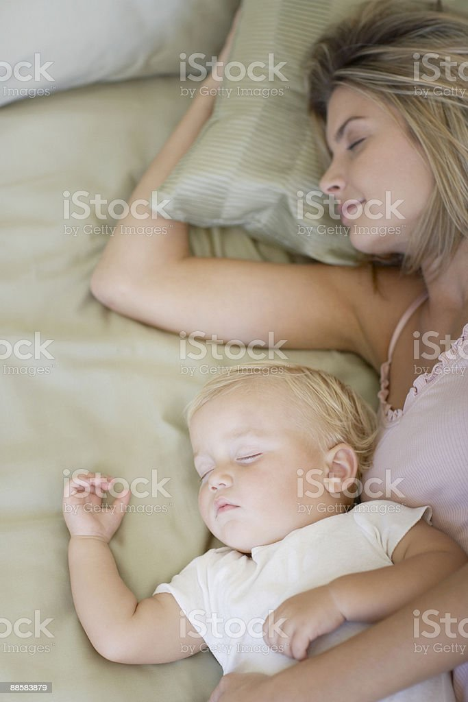 Mother and baby sleeping in bed royalty-free stock photo