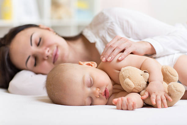 mother and baby sleeping together in a bedroom stock photo