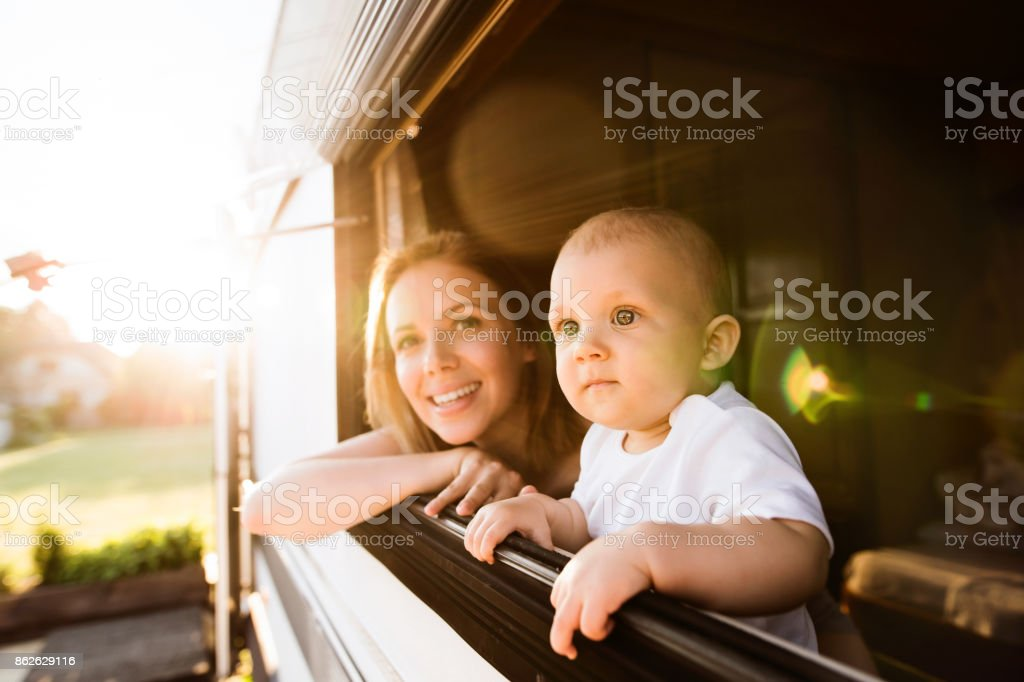 Mother and baby son in a camper van. stock photo